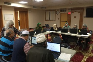 Muslim elders at India Home's Desi Senior Center use a manual in Bengali to learn computers