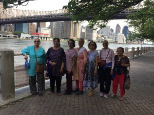 Elders pose In the shadow of the Queensboro Bridge on Roosevelt Island